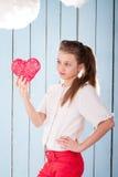 Muchacha que lleva a cabo el corazón rojo y que mira en él Fotos de archivo libres de regalías