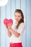 Muchacha que lleva a cabo el corazón rojo y que mira la cámara Imagen de archivo