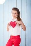 Muchacha que lleva a cabo el corazón rojo y que mira la cámara Imagen de archivo libre de regalías