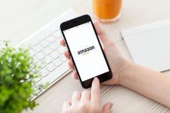 Muchacha que lleva a cabo el espacio del iPhone 6 gris con el servicio el Amazonas Imagen de archivo