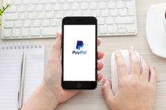 Muchacha que lleva a cabo el espacio del iPhone 6 gris con el servicio Paypal Imagen de archivo libre de regalías