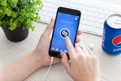 Muchacha que lleva a cabo el espacio del iPhone 6 gris con el servicio Shazam de la música Fotos de archivo libres de regalías