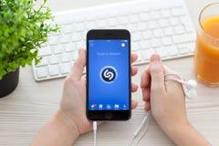 Muchacha que lleva a cabo el espacio del iPhone 6 gris con el servicio Shazam de la música Foto de archivo libre de regalías