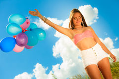 Muchacha que lleva a cabo el fondo del cielo de los globos Imágenes de archivo libres de regalías
