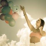 Muchacha que lleva a cabo el fondo del cielo de los globos Imagenes de archivo