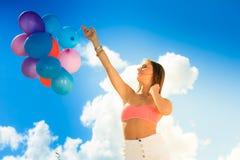 Muchacha que lleva a cabo el fondo del cielo de los globos Foto de archivo libre de regalías