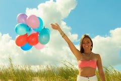 Muchacha que lleva a cabo el fondo del cielo de los globos Imagen de archivo libre de regalías