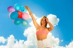 Muchacha que lleva a cabo el fondo del cielo de los globos Fotografía de archivo