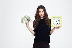 Muchacha que lleva a cabo el reloj de pared y cuentas de dólares fotos de archivo libres de regalías