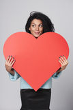 Muchacha que lleva a cabo forma roja grande del corazón Imagen de archivo