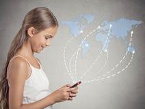 Muchacha que lleva a cabo Internet de la ojeada del smartphone por todo el mundo Imagen de archivo libre de regalías