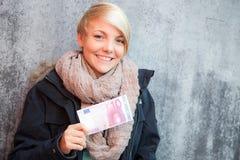 Muchacha que lleva a cabo la nota del euro diez Imágenes de archivo libres de regalías