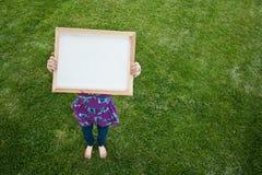 Muchacha que lleva a cabo la pequeña muestra blanca Imagen de archivo