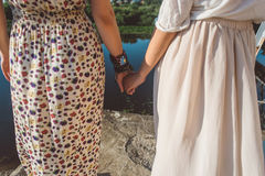Muchacha que lleva a cabo las manos en el primer de la orilla del río Foto de archivo libre de regalías