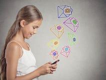Muchacha que lleva a cabo mandar un SMS del smartphone, enviando el mensaje Imagen de archivo libre de regalías