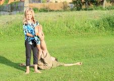 Muchacha que lleva a cabo a pies de un muchacho Foto de archivo libre de regalías