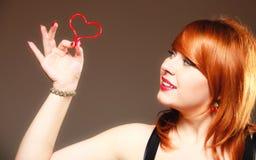 Muchacha que lleva a cabo símbolo rojo del amor del corazón de la tarjeta del día de San Valentín Rose roja Foto de archivo