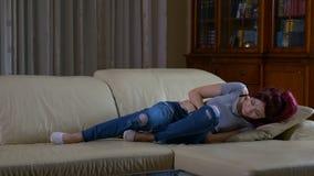 Muchacha que lleva a cabo sus manos sobre su vientre que tiene dolor abdominal severo que siente enfermo almacen de metraje de vídeo
