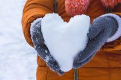 Muchacha que lleva a cabo un corazón de la nieve, deseos para felicitar a su amigo Fotos de archivo libres de regalías