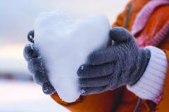 Muchacha que lleva a cabo un corazón de la nieve, deseos para felicitar a su amigo Fotografía de archivo libre de regalías
