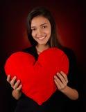 Muchacha que lleva a cabo un corazón grande de la felpa Fotografía de archivo libre de regalías