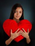 Muchacha que lleva a cabo un corazón grande de la felpa Fotos de archivo libres de regalías
