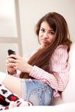 Muchacha que lleva a cabo un gruñón contra el teléfono móvil Fotografía de archivo libre de regalías