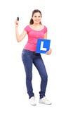 Muchacha que lleva a cabo un l muestra y una llave del coche Imagen de archivo