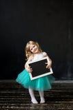 Muchacha que lleva a cabo un tablero de tiza negro con el espacio en blanco vacío para usted Foto de archivo