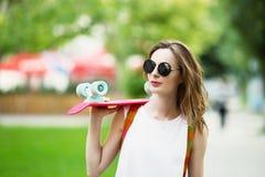 Muchacha que lleva a cabo un tablero plástico del patín al aire libre Foto de archivo libre de regalías