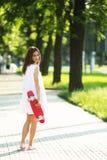 Muchacha que lleva a cabo un tablero plástico del patín al aire libre Fotografía de archivo libre de regalías