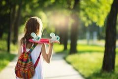 Muchacha que lleva a cabo un tablero plástico del patín al aire libre Imagen de archivo libre de regalías