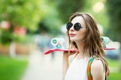 Muchacha que lleva a cabo un tablero plástico del patín al aire libre Fotos de archivo