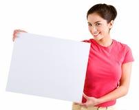 Muchacha que lleva a cabo una muestra blanca en blanco Imágenes de archivo libres de regalías