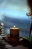 Muchacha que lleva a cabo una vela cerca de un árbol de navidad Fotografía de archivo