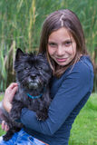 Muchacha que lleva el perro negro en el brazo en naturaleza Foto de archivo