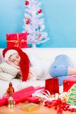 Muchacha que lleva el sombrero de santa que duerme en el sofá en casa Fotos de archivo libres de regalías