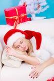 Muchacha que lleva el sombrero de santa que duerme en el sofá en casa Imágenes de archivo libres de regalías