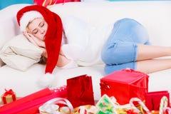 Muchacha que lleva el sombrero de santa que duerme en el sofá en casa Imagen de archivo