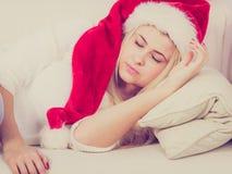 Muchacha que lleva el sombrero de santa que duerme en el sofá en casa Foto de archivo libre de regalías