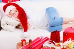 Muchacha que lleva el sombrero de santa que duerme en el sofá en casa Foto de archivo