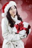Muchacha que lleva el sombrero de santa que sostiene la caja de regalo Fotografía de archivo libre de regalías