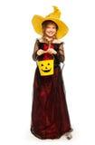 Muchacha que lleva el traje de la bruja de Halloween con el cubo Imagen de archivo libre de regalías