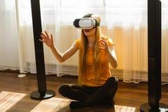 Muchacha que lleva gafas de la realidad virtual en casa Fotos de archivo