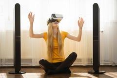 Muchacha que lleva gafas de la realidad virtual en casa Fotografía de archivo