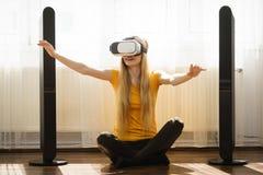 Muchacha que lleva gafas de la realidad virtual en casa Imagen de archivo