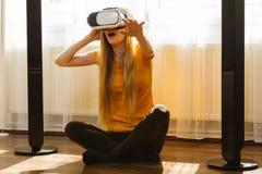 Muchacha que lleva gafas de la realidad virtual en casa Fotografía de archivo libre de regalías