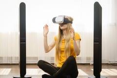 Muchacha que lleva gafas de la realidad virtual en casa Fotos de archivo libres de regalías
