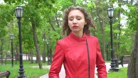 Muchacha que lleva la chaqueta de cuero roja que mastica el chicle Un día nublado del otoño en el parque verde metrajes