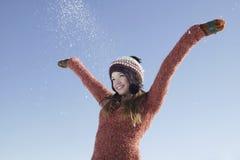 Muchacha que lleva la ropa caliente con los brazos extendidos en nieve Imagen de archivo